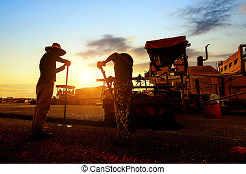 Road workers - Sunset, when the work of the workers, asphalt...