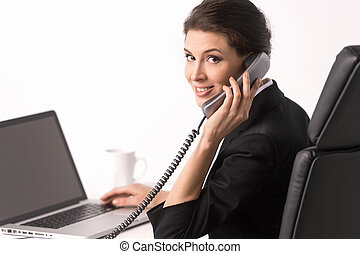 Talking at phone. Confident middle-aged businesswoman sitting at her working place and looking over shoulder