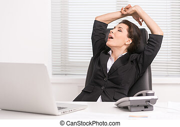 Businesswoman yawning. Tired middle-aged businesswoman sitting at her working place and yawning