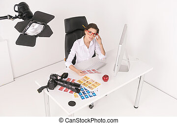 Creative businesswomen. Top view of confident middle-aged businesswoman sitting at her working place and looking at camera