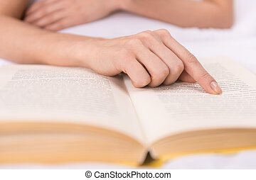 Reading a book. Close-up of finger pointing the book