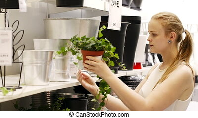 Young blond woman looking at vases with plants in a shop -...