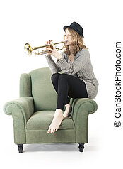 young pretty woman playing the trumpet sitting on armchair -...