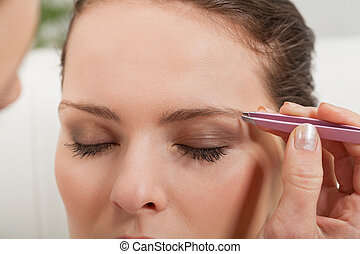 young beautiful woman eyebrow plucking tweezers eyes hair...
