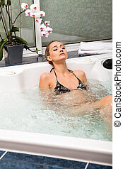 attractive blonde woman relaxing in jacuzzi whirlpool spa...