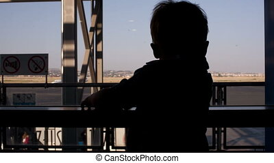 Young boy looking through window in the airport - Silhouette...