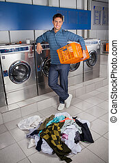Happy Man Holding Empty Basket With Dirty Clothes On Floor -...