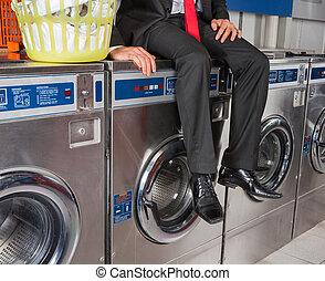 Businessman Sitting On Washing Machine
