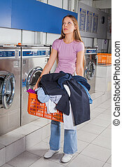 Woman Holding Basket Full Of Dirty Clothes - Full length of...