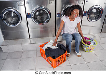 Woman With Baskets Of Dirty Clothes Sitting At Laundromat -...