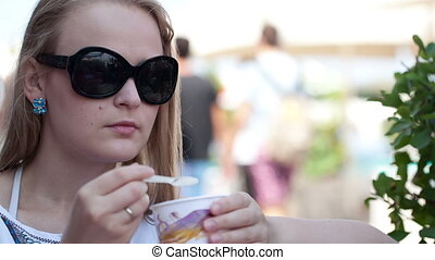 Woman eating ice cream in the street cafe