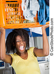 Woman Carrying Basket Of Dirty Clothes - Young African...
