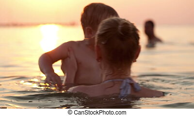 Mother and son swim in the sea - Happy young mother plays...