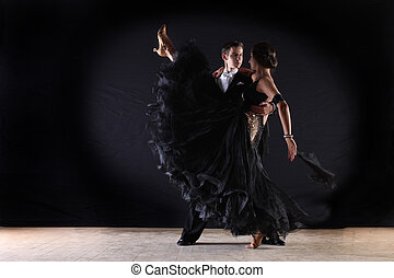 Latino dancers in ballroom against on black background