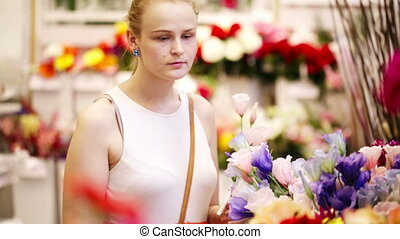 Beautiful young lady buying fresh flowers