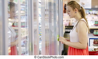 Young woman at the supermarket - Young woman buying dairy or...