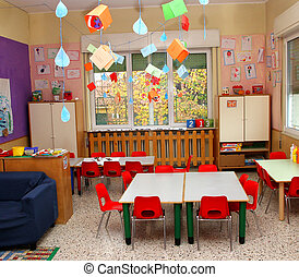 classroom in a kindergarten with tables and red chairs -...
