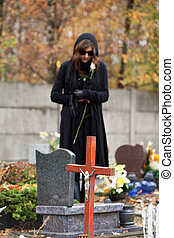 Grieving woman at cemetery in autumn - Woman in black...