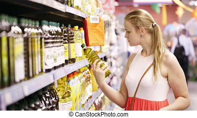 Young woman buying olive oil - Young blond woman picking an...