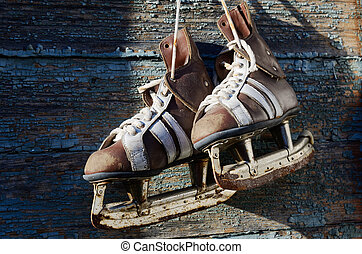 vintage pair of mens ice skates hanging on a wooden wall...