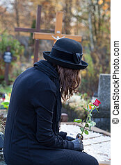 Widow at cemetery in autumn - Woman dressed in black sitting...
