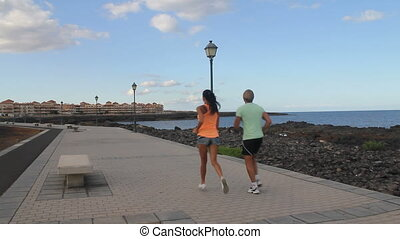 couple jogging along the shoreline - Young couple jogging...