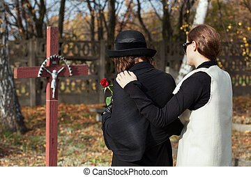 Two women at cemetery in fall - Two women grieving following...