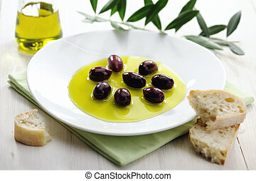 Olive Oil and Black Olives on a Plate with Bread; Italian Appetizer