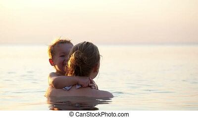 Loving mother hugging with her son in the sea