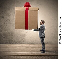 Big present - Elegant businessman holding a big Christmas...
