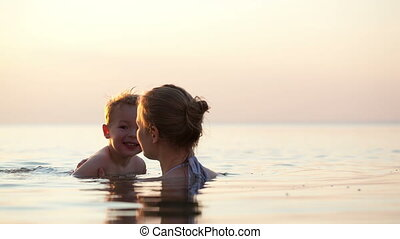 Young mother teaches her little son to swim in the sea near...
