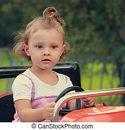 Funny thinking kid girl driving car in recreation park on summer background. Closeup portrait