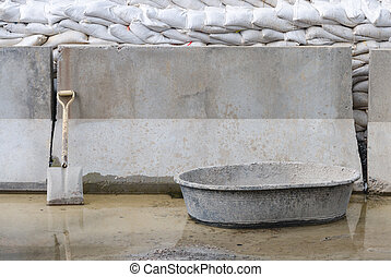 shovel leaning against wall with concrete mixing container...