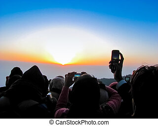 Crowd photographing the sunrise - Group of people...