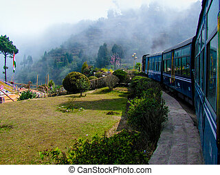 Train passing a garden and entering fog - Train passing a...