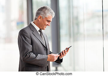 mid age businessman using tablet computer in modern office