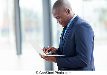 african american businessman working on laptop in modern...