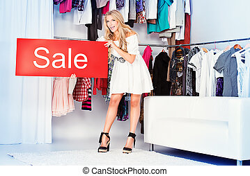 advertising - Fashionable young woman shopping in a clothing...