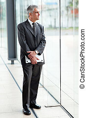 thoughtful senior businessman holding a laptop in modern...