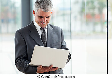 senior businessman using laptop computer - happy senior...