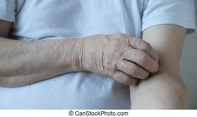 man with itchy arm - a man scratches his upper arm