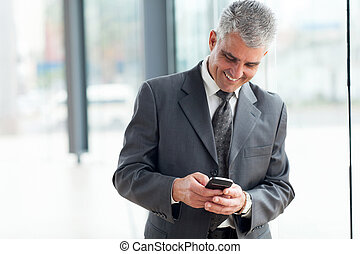 mid age businessman using smart phone - cheerful mid age...