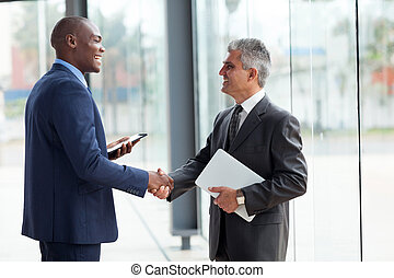 businessmen handshaking - two cheerful businessman...