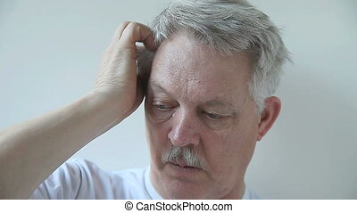 man scratching his scalp - senior man has an irritation on...