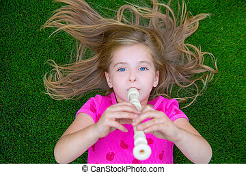 Blond kid children girl playing flute lying on grass...
