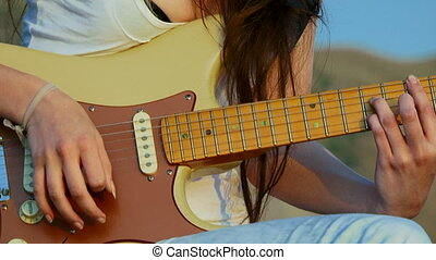 Guitar chords - Young woman playing guitar. Close-up