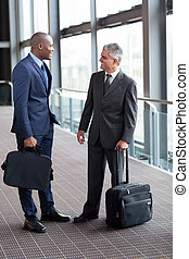 businessmen talking at airport - two friendly businessmen...