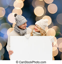 couple in winter clothes with blank white board - christmas,...