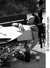 Drunk on park bench - Drunk guy sleeping on a park bench, a...