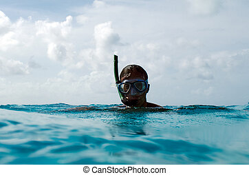 Snorkeler in a turquoise lagoon - Young snorkeler man...